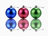 Three Christmas tree baubles and their reflections