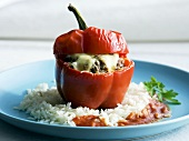 A pepper stuffed with minced meat and cheese on a bed of rice