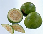 Two whole guavas and one cut open