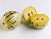 A pepino melon beside two pepino melon halves