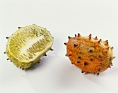 One whole kiwano beside a kiwano half
