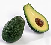 Eine ganze Avocado neben einer Avocadohälfte