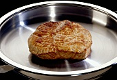 Piece of fried meat in a frying pan