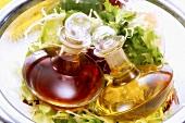 Oil and vinegar bottles lying on green salads