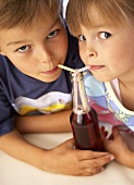 Children drinking fizzy drink through straws