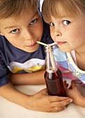 Children drinking fizzy drink through straws
