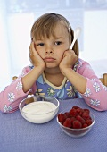 Girl sitting petulantly in front of yoghurt & raspberries