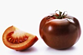 A whole tomato and a wedge of tomato, variety 'Kumato'
