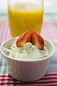 Cottage cheese with strawberry in front of orange juice