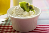 Cottage cheese and pieces of kiwi fruit in a small bowl