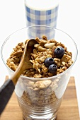 Crunchy muesli with blueberries and wooden spoon in a glass