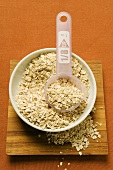 Rolled oats in a bowl with plastic measuring spoon