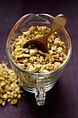 Crunchy muesli with wooden spoon in a measuring jug