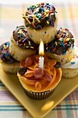 Assorted muffins, one with birthday candle