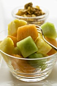 Exotic fruit salad in glass bowl, cereal behind