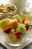 Fruit salad, cereal and honey for a healthy breakfast