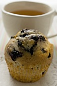 Blueberry muffin in front of a cup of tea
