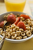 Breakfast cereal rings and strawberry halves in a bowl