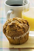 Muffin, orange juice and coffee behind