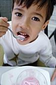 Small boy eating strawberry quark