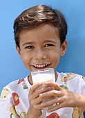 Small boy drinking a glass of milk