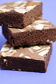 Three brownies with almonds in a pile