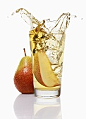 Wedge of pear falling into a glass of pear juice