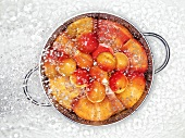 Apricots in a colander being sprayed with water