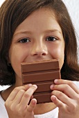 Small girl eating a bar of chocolate