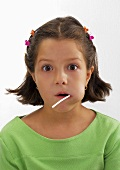 Small girl with lollipop in her mouth