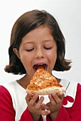Small girl biting into a slice of pizza