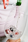 Pouring champagne onto berry ice cubes in glass