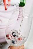 Beeren-Eiswürfel im Glas, Champagner eingiessen
