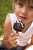 Small child holding an ice cream on a stick