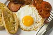 English breakfast with bacon, fried egg and tomato