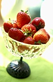 Fresh strawberries in a stemmed glass bowl