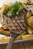 Grilled pork chop on roast potatoes