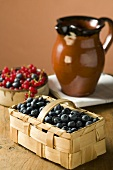 Blueberries in a basket and small bowl of mixed berries