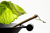 Savoy cabbage leaf falling into a wok