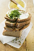 Several slices of bread in a pile with butter and chives