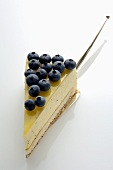 A piece of lemon cream cake with blueberries