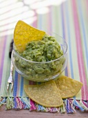 Guacamole in a small glass bowl with nachos