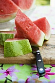 Watermelon, cut into pieces, on a wooden board