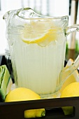 Lemonade in a glass jug with slices of lemon