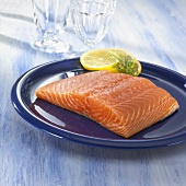 A salmon fillet with slices of lemon on a plate