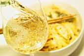 Ein Glas Weisswein eingießen