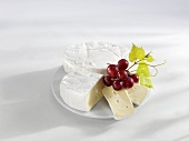 Two rounds of Camembert and grapes on a plate