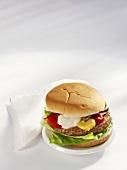 A hamburger with mustard, ketchup and mayonnaise