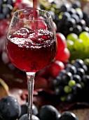 Ein Glas Rotwein eingießen mit Trauben im Hintergrund