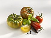 Various types of tomatoes with basil and bunch of pepper